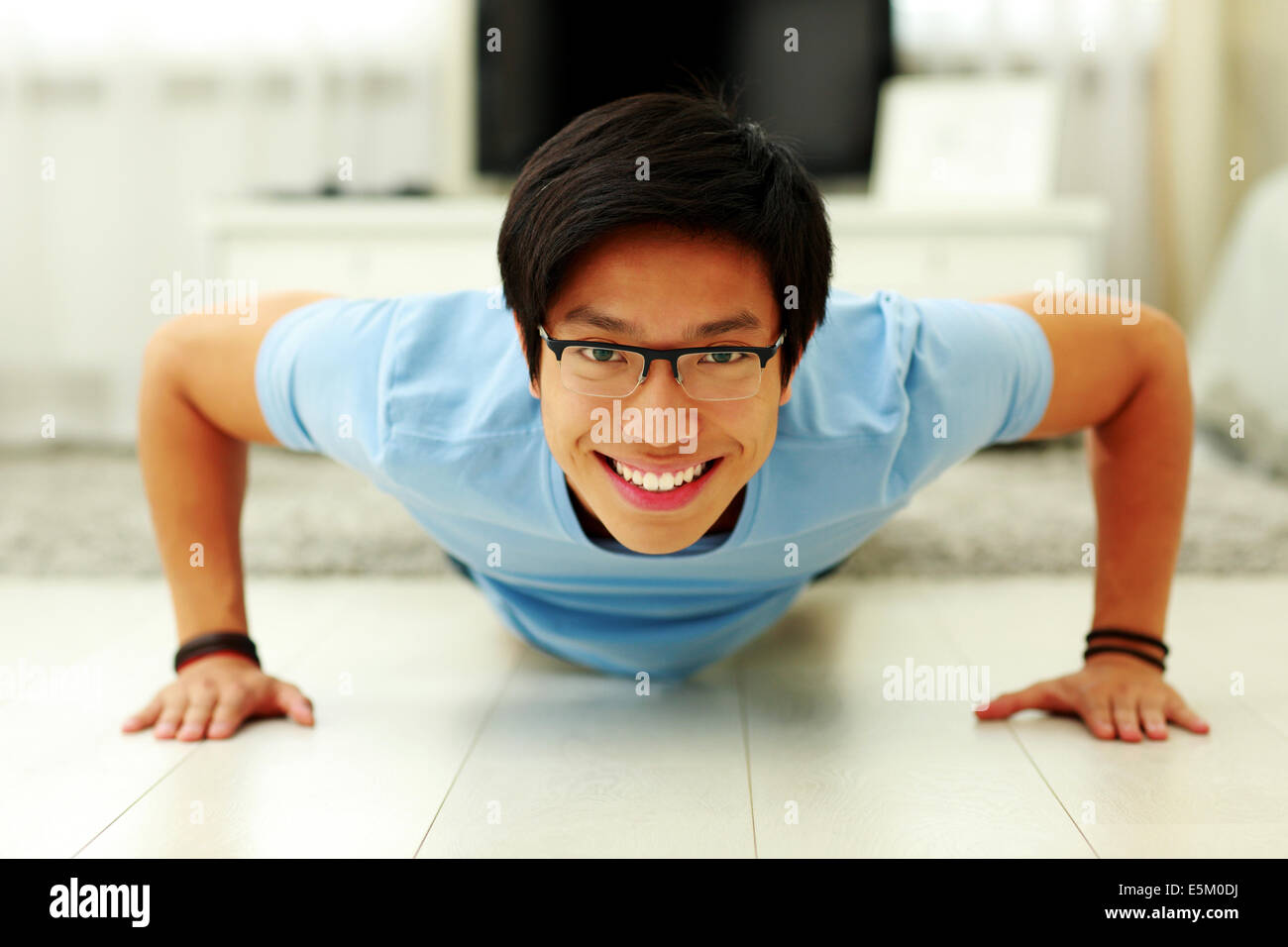 Portrait of a happy young man doing push ups in the living room at home - Stock Image