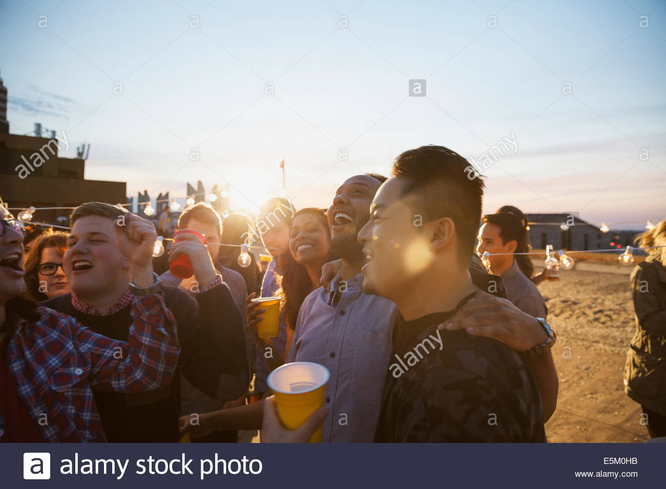 Friends enjoying urban rooftop party - Stock Image