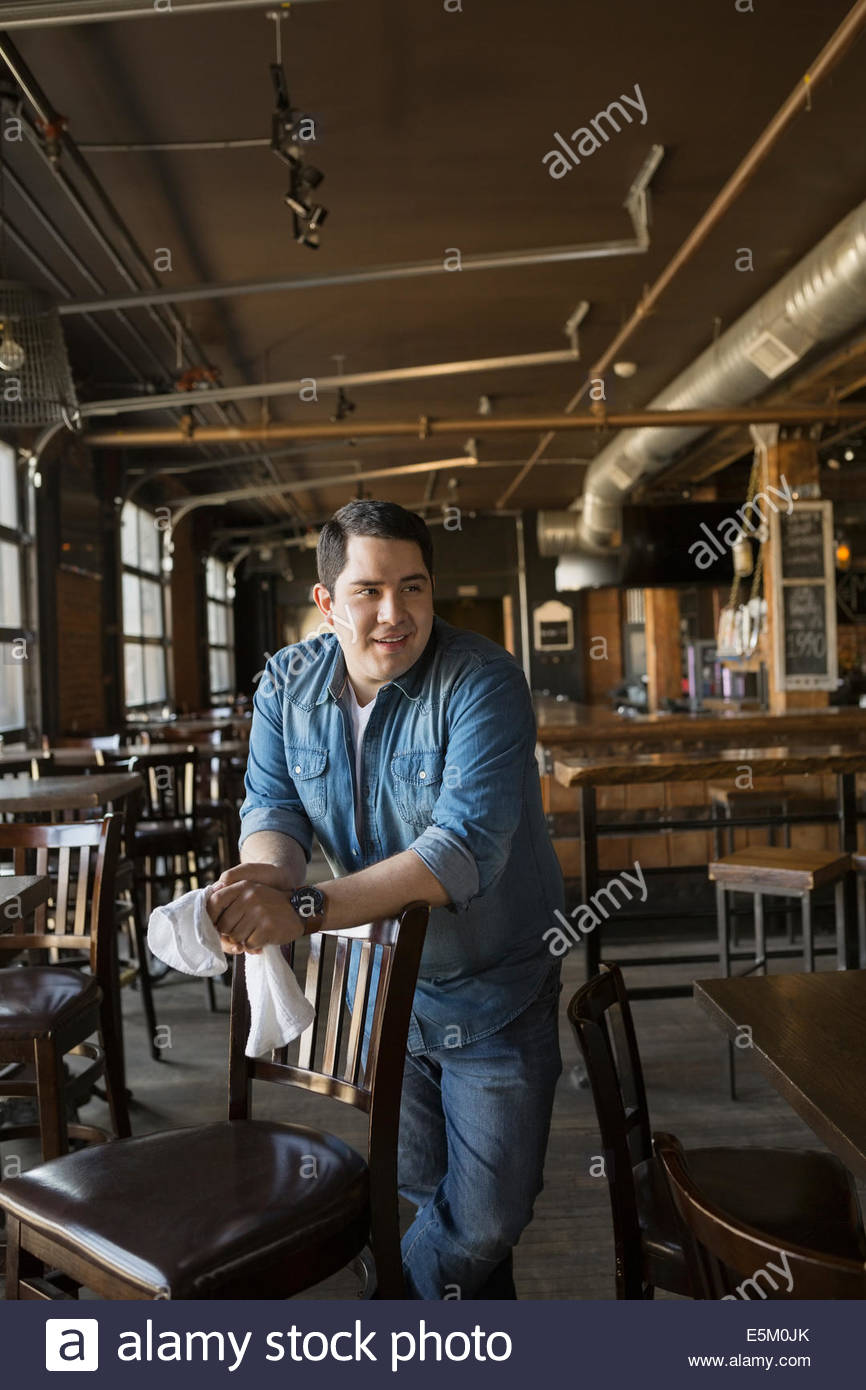 Smiling pub owner leaning on chair - Stock Image