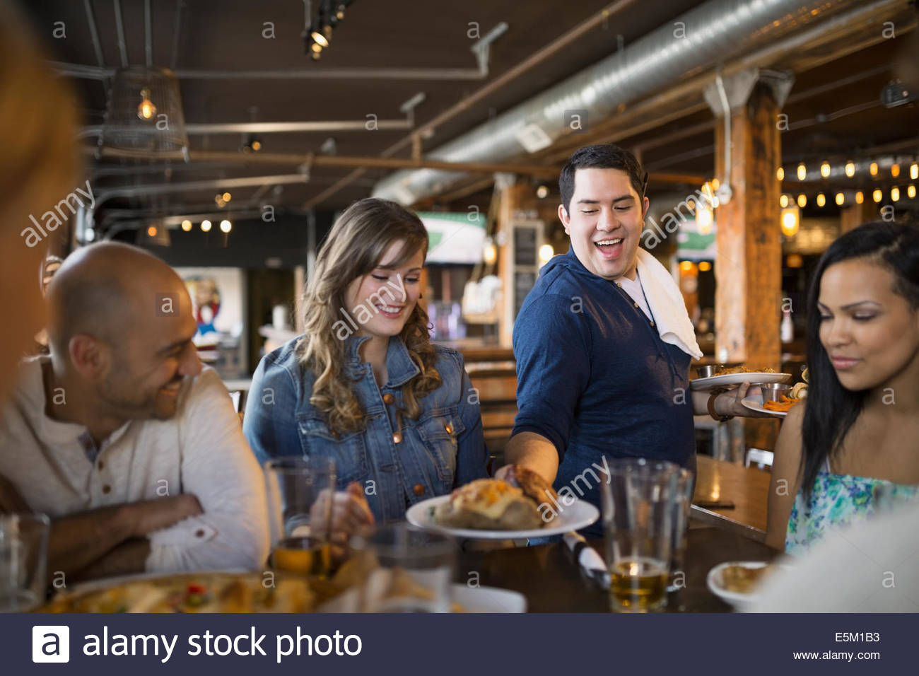 Waiter serving food to friends in pub - Stock Image