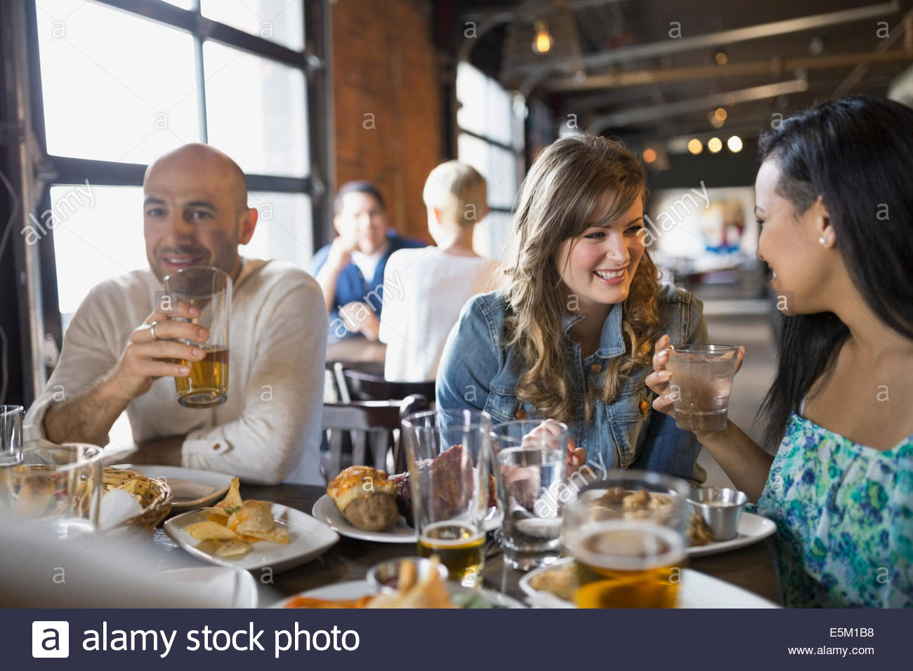 Friends talking and eating in pub - Stock Image