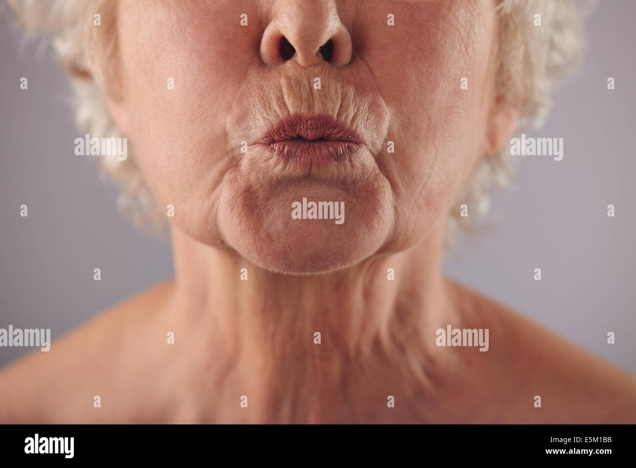 Close-up portrait of mature woman puckering lips against grey background. Senior woman grimacing. Focus on lips. - Stock Image