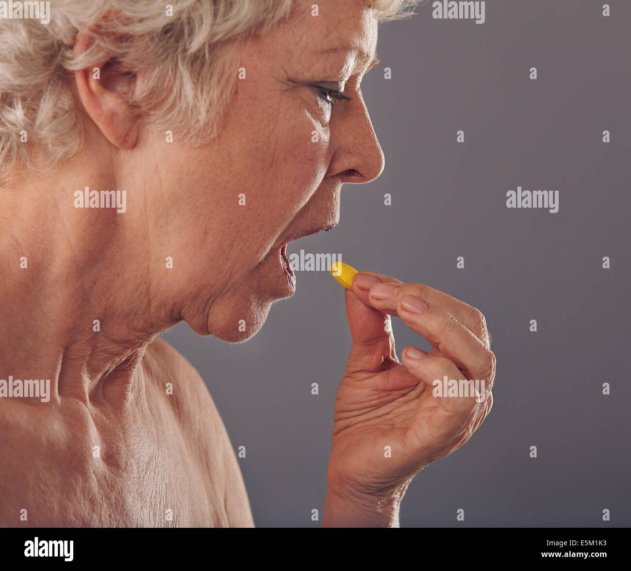 Side view of mature woman taking a tablet against grey background. Time for medication. Old woman having a medicine - Stock Image