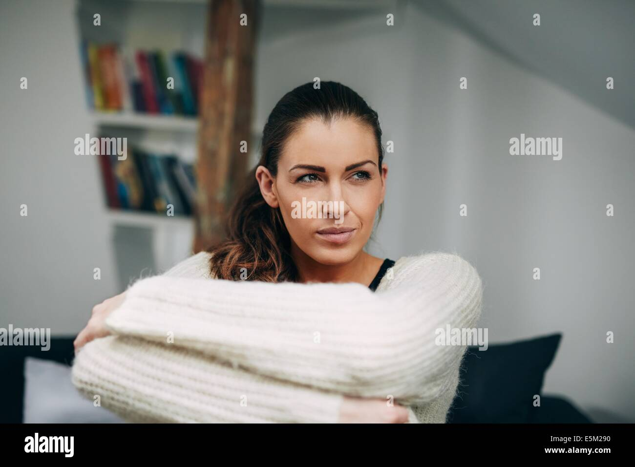 Portrait of young lady sitting alone on sofa looking away. Caucasian female model at home daydreaming. - Stock Image