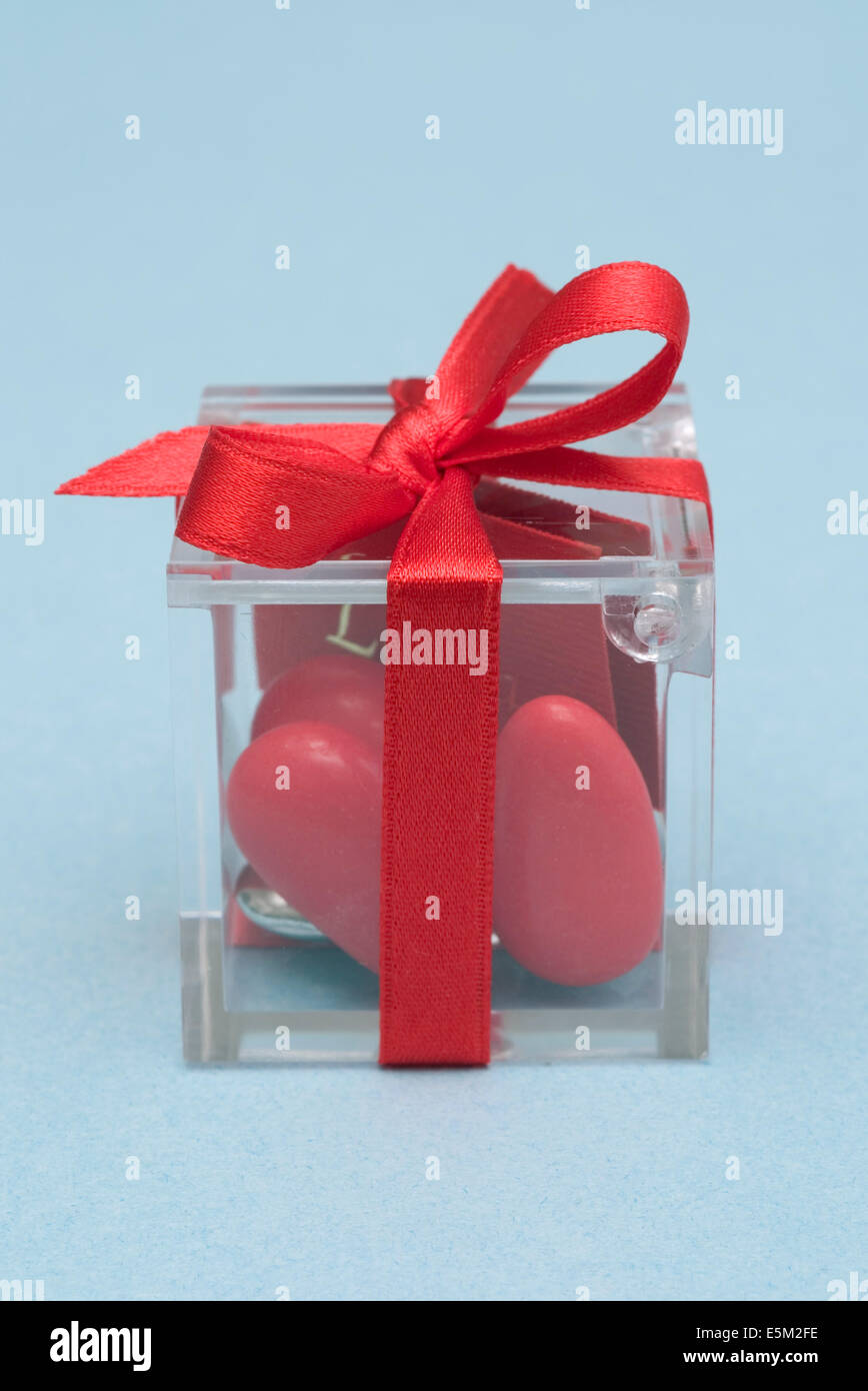 transparent box with red sugarcoated almonds and red ribbon - Stock Image