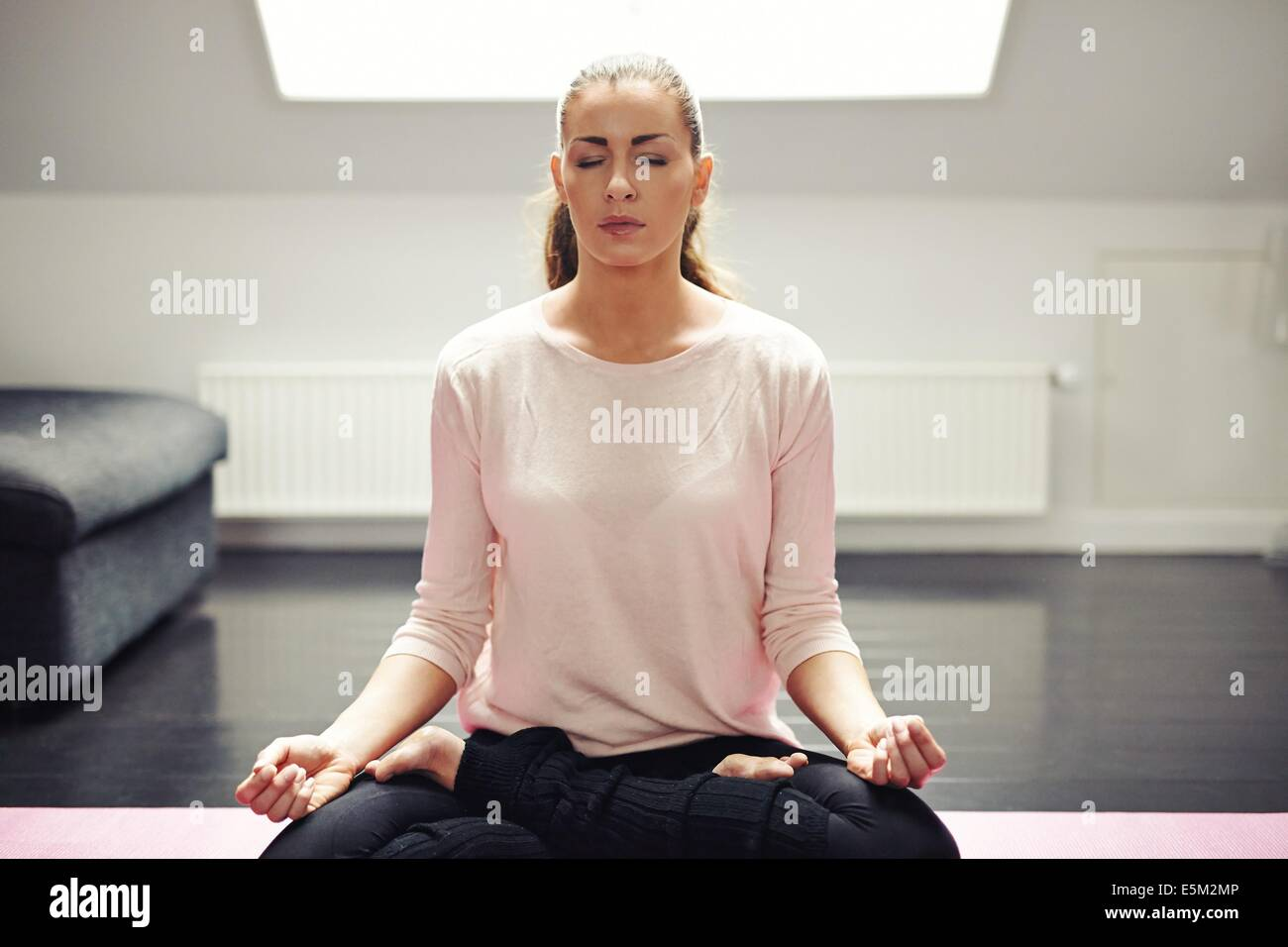 Portrait of beautiful woman exercise. Relaxing at home with yoga workout. Fit caucasian female model in meditation. - Stock Image