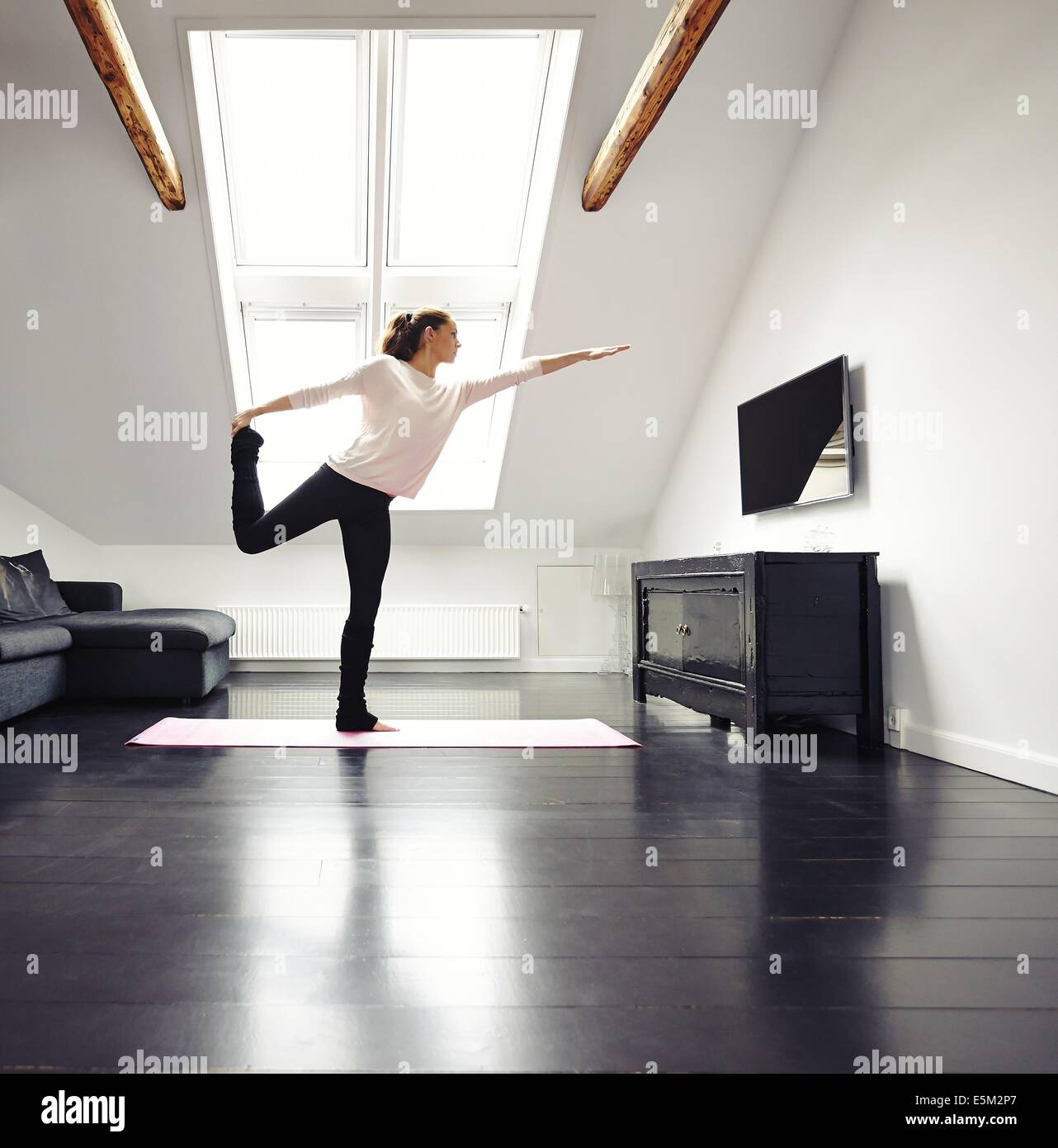 Beautiful woman practicing yoga exercises in living room. Fit female standing on one leg exercising at home. - Stock Image