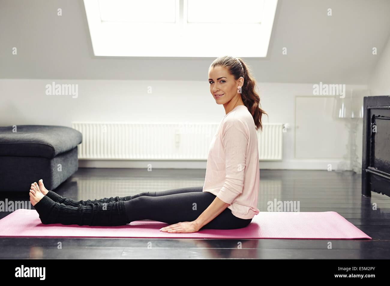 Portrait of fresh young woman sitting on exercise mat looking at camera smiling. Beautiful female exercising in Stock Photo