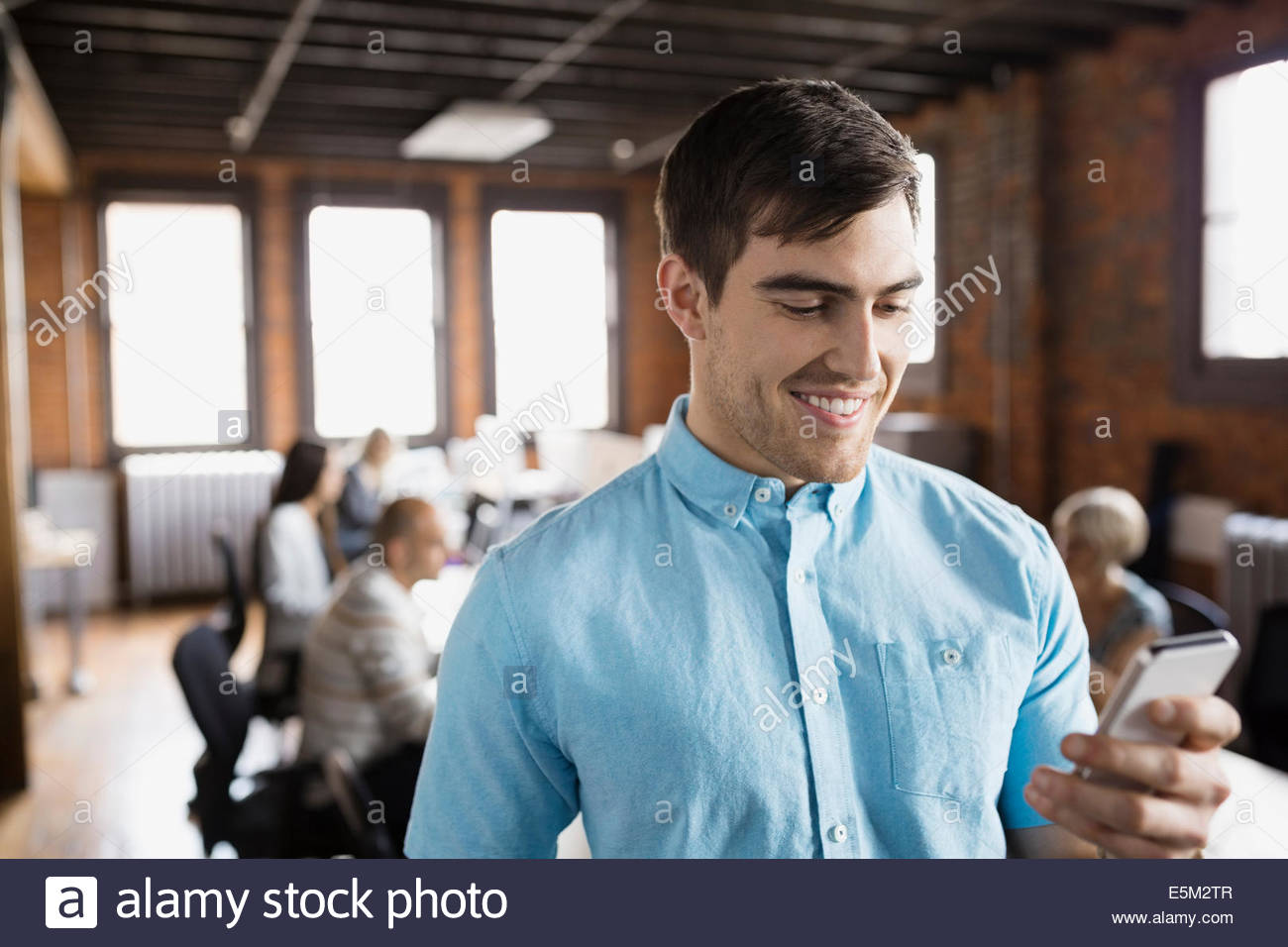 Businessman using cell phone in office Stock Photo