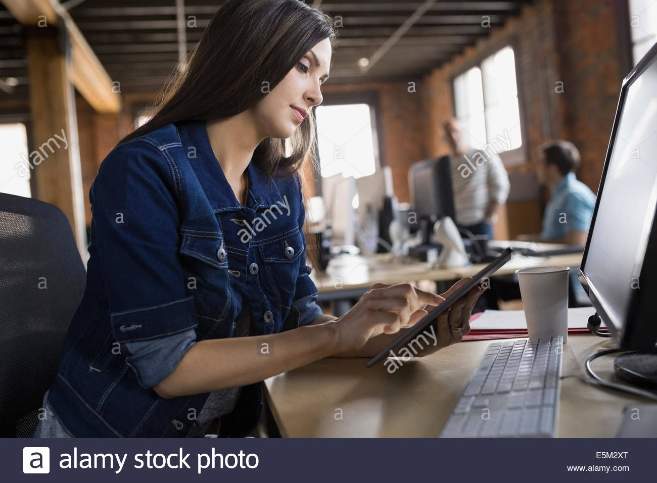 Businesswoman using digital tablet at desk in office - Stock Image