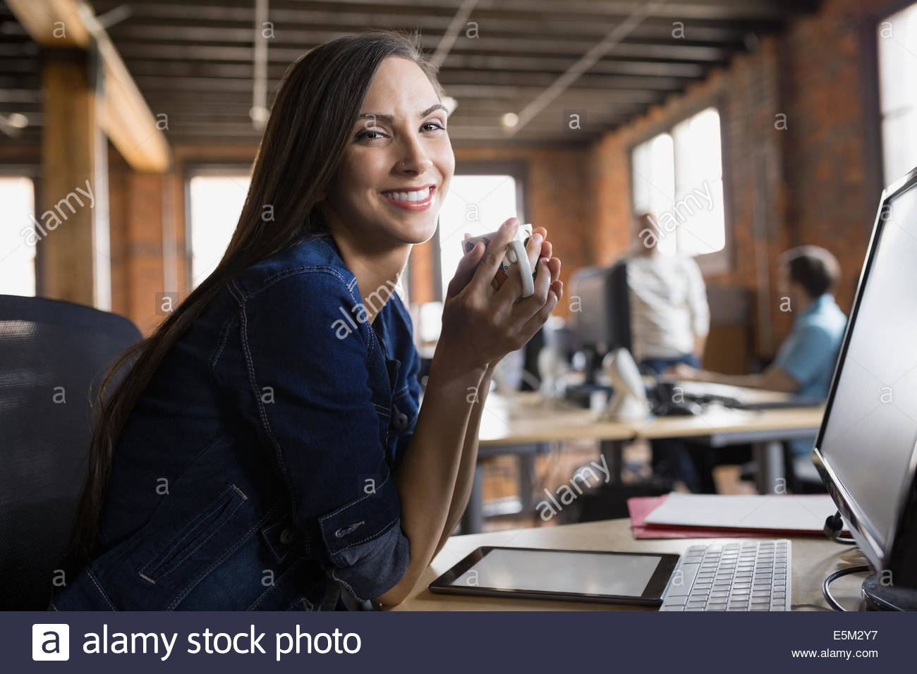 Portrait of smiling businesswoman drinking coffee in office - Stock Image