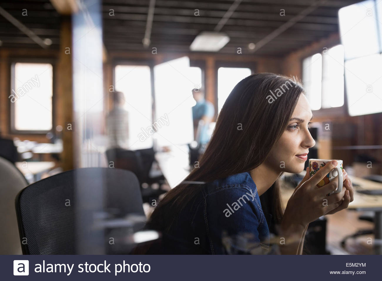 Pensive businesswoman drinking coffee in office - Stock Image