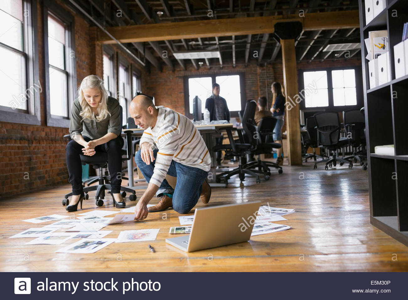Business people reviewing proofs on floor in office - Stock Image