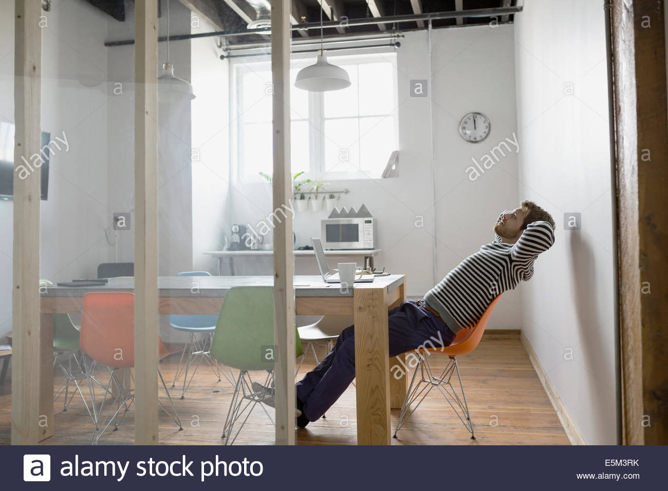 Businessman leaning back in chair in office - Stock Image