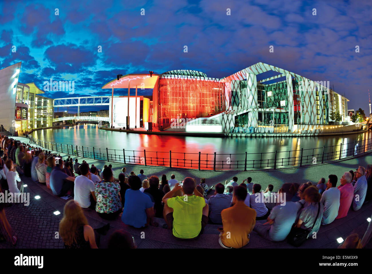 Germany, Berlin: Tourists watching nocturnal video documentary about the history of the Reichstag  at Spree riverside - Stock Image