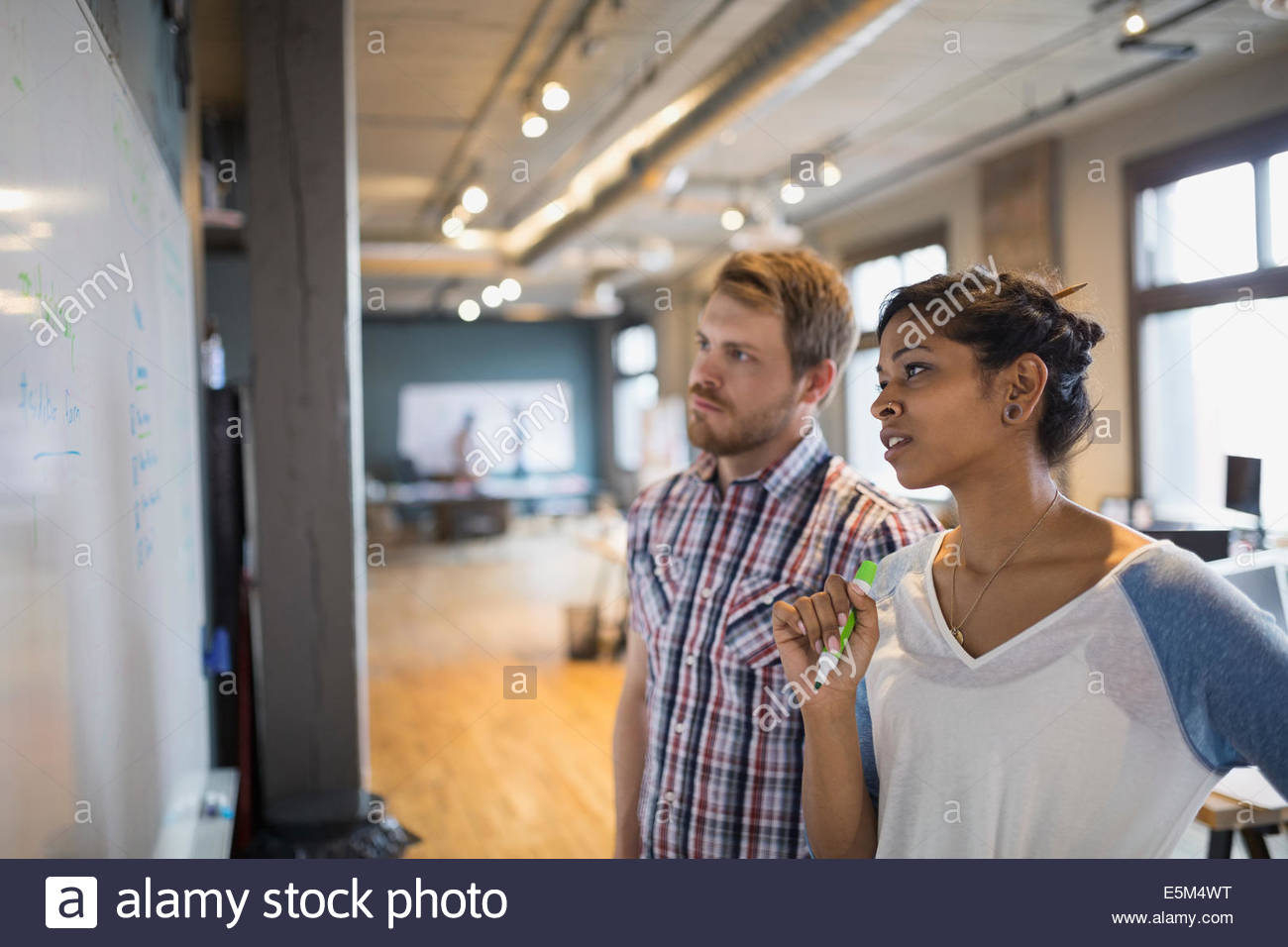 Business people talking at whiteboard in office - Stock Image