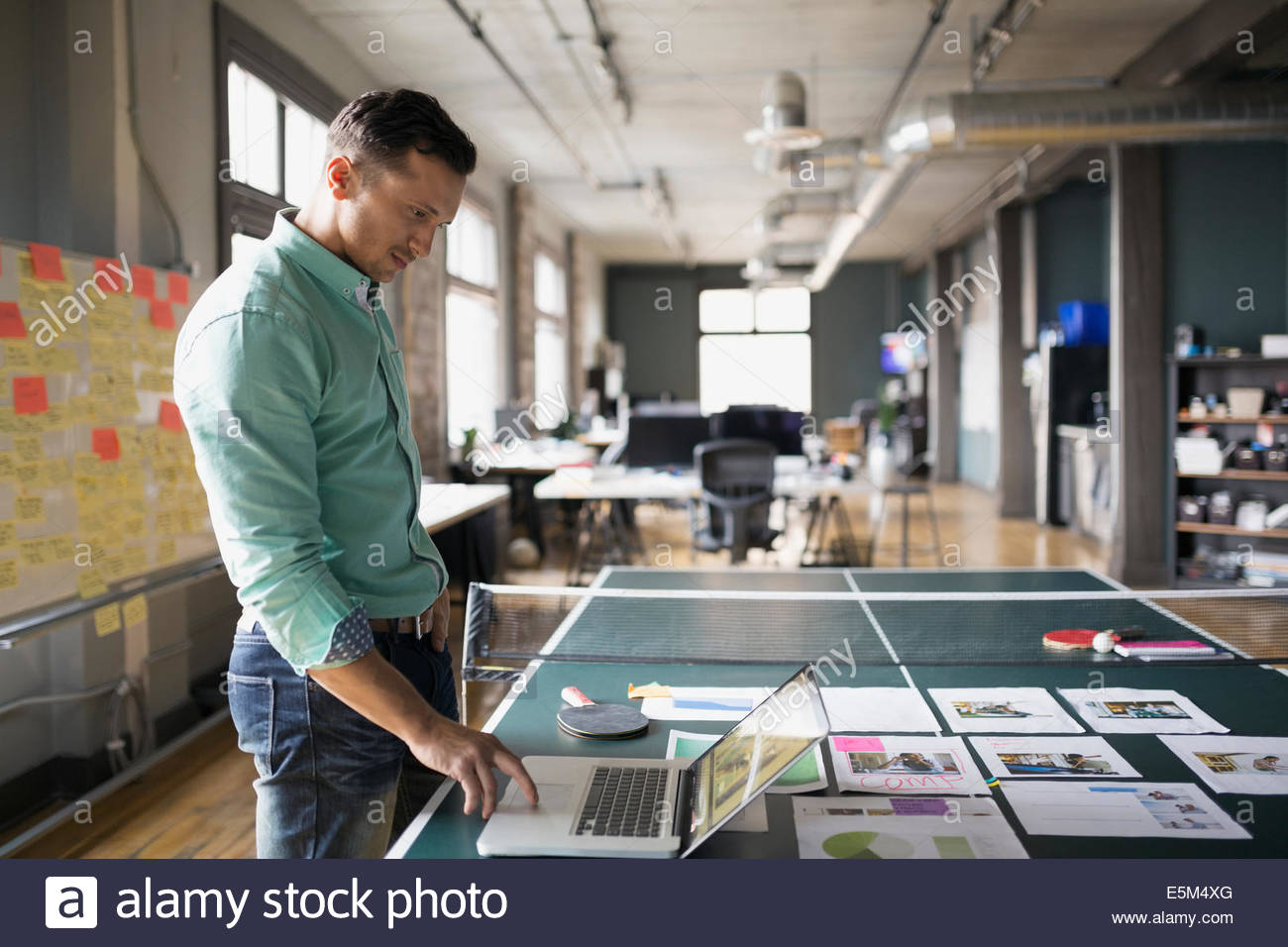 Creative businessman using laptop on ping pong table - Stock Image