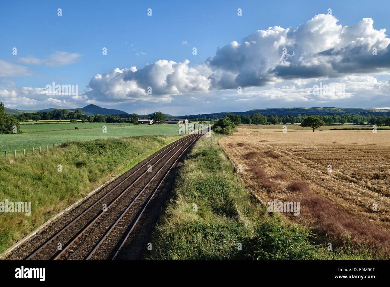 The Welsh Marches railway line looking south towards Caer Caradoc and the Long Mynd in Shropshire, UK - Stock Image