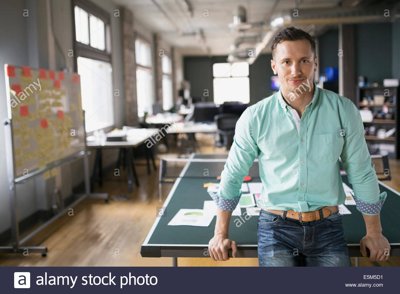 Creative businessman leaning on ping pong table - Stock Image