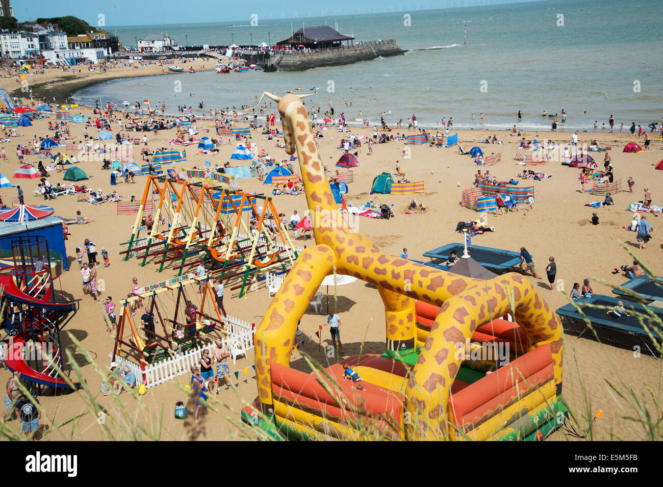 Broadstairs, Kent. Crowded beach with swings and bouncy giraffe - Stock Image