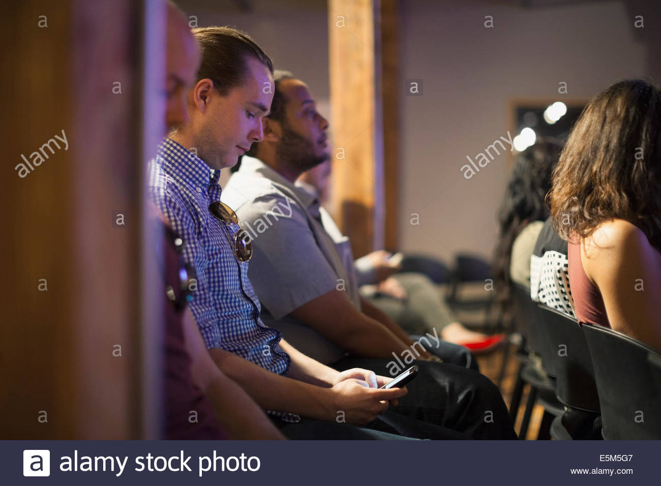Man in audience checking cell phone - Stock Image