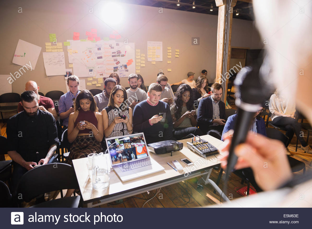 People in audience checking cell phones during presentation - Stock Image