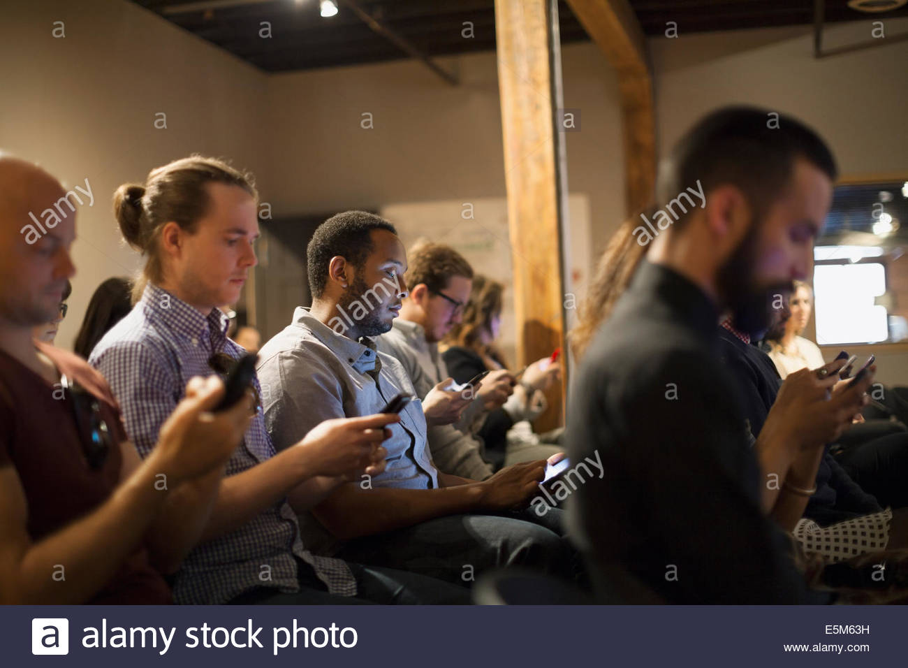 People in audience checking cell phones - Stock Image