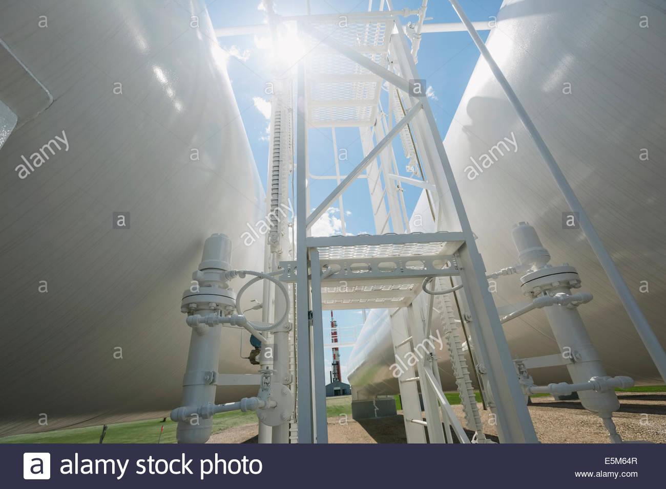 Sun shining over natural gas tanks - Stock Image
