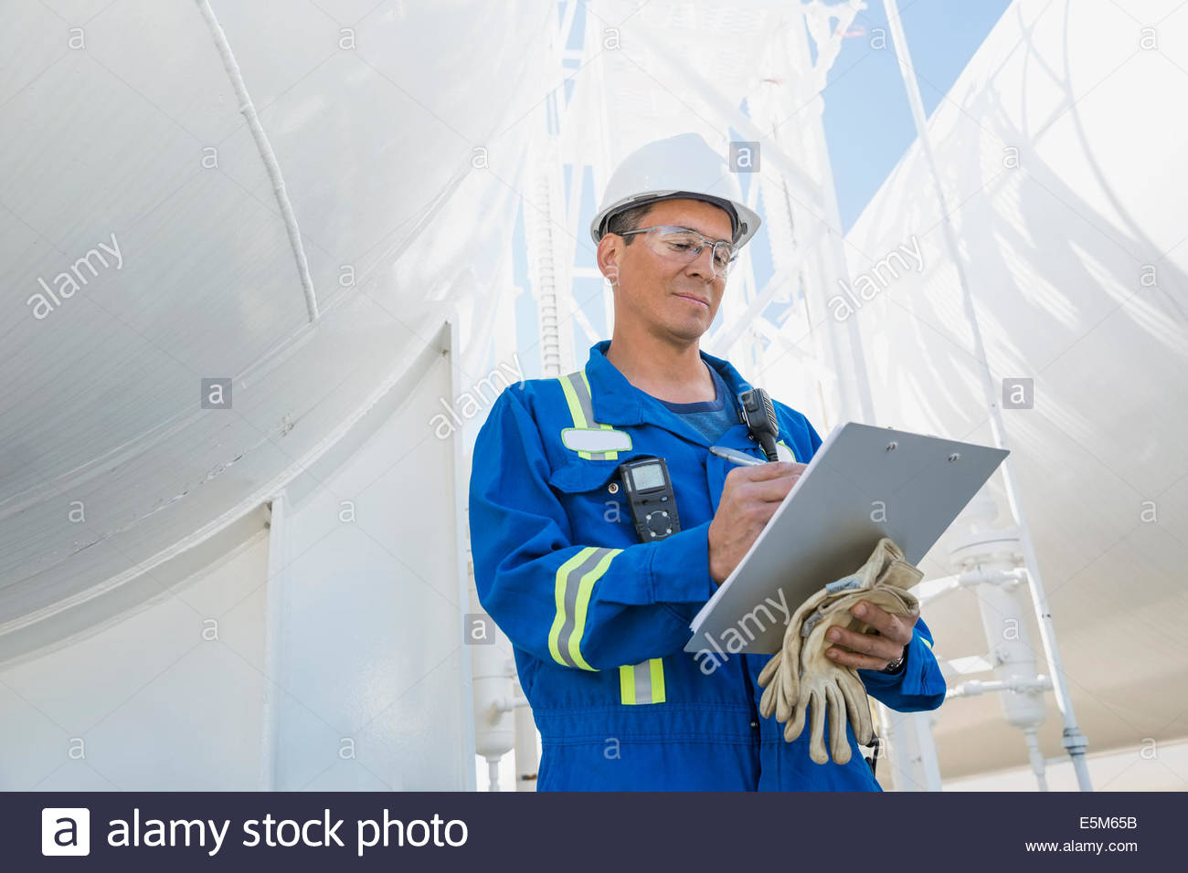 Male worker with clipboard at gas plant - Stock Image