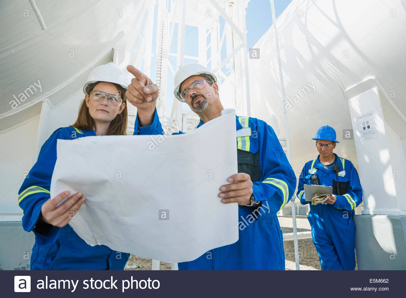 Workers with blueprints at gas plant - Stock Image
