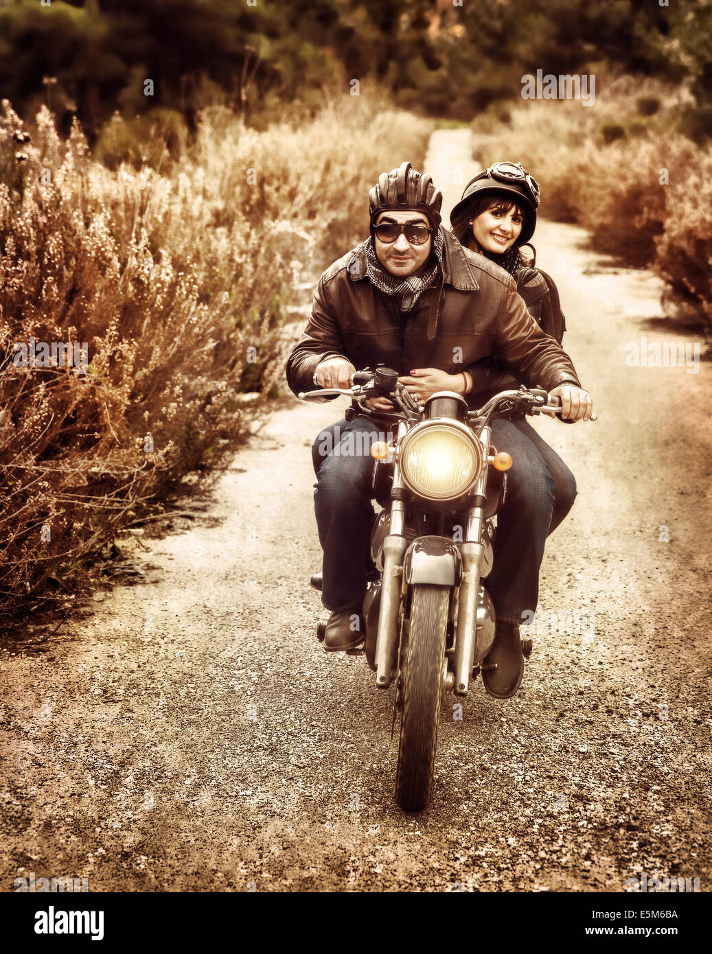 Vintage style image of two happy bikers riding on the road, active family enjoying journey on luxury extreme transport - Stock Image