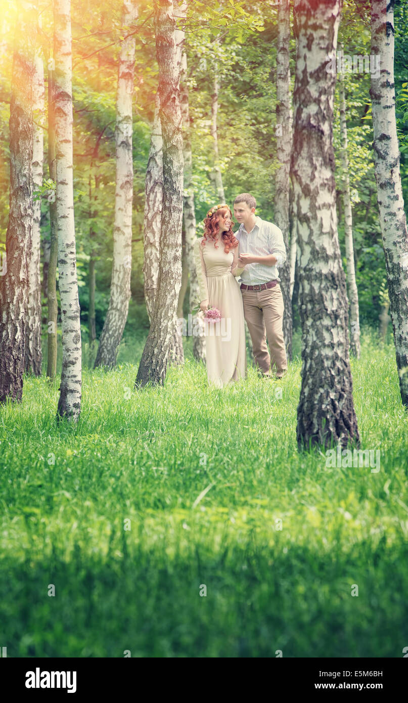 Loving couple walking between birch in the park in sunny day,  holding hands, happy wedding day, love and romance - Stock Image