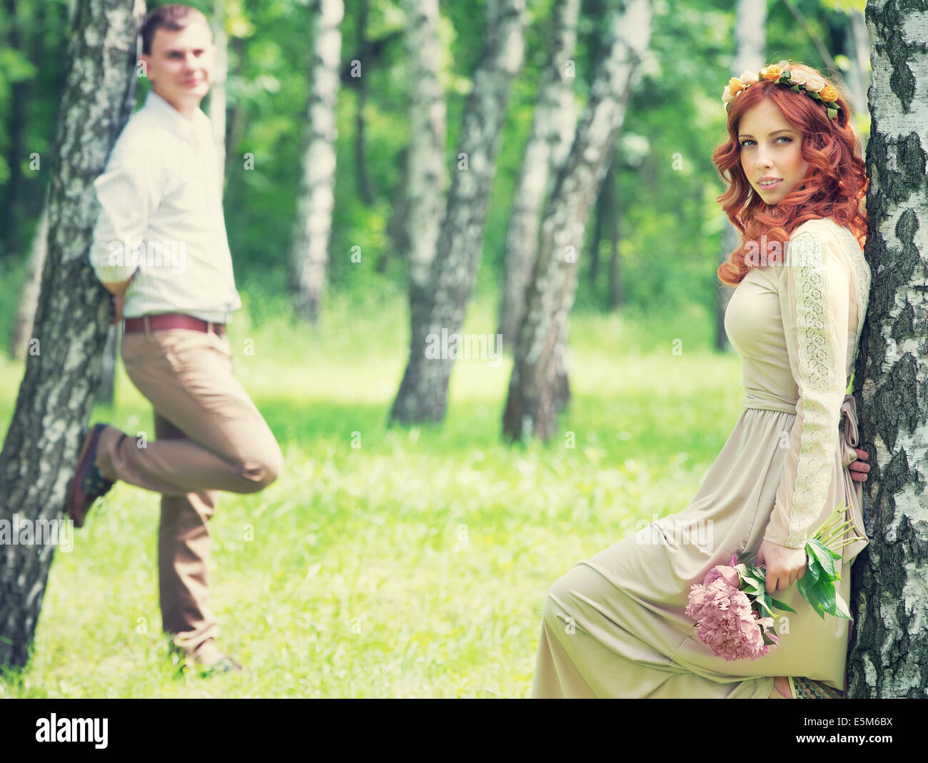 Romantic gentle bride and handsome groom posing near birch trees, beautiful young loving couple, summer time, happy - Stock Image