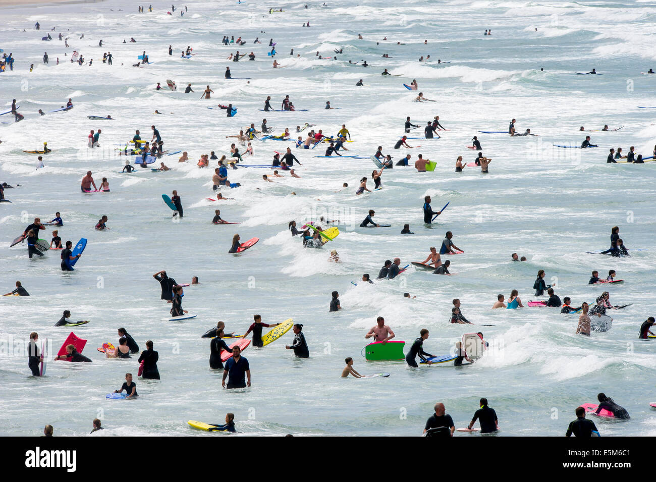 Sunbathers cool off in the sea on the busiest day of the year at Woolacombe beach, Devon, UK Stock Photo