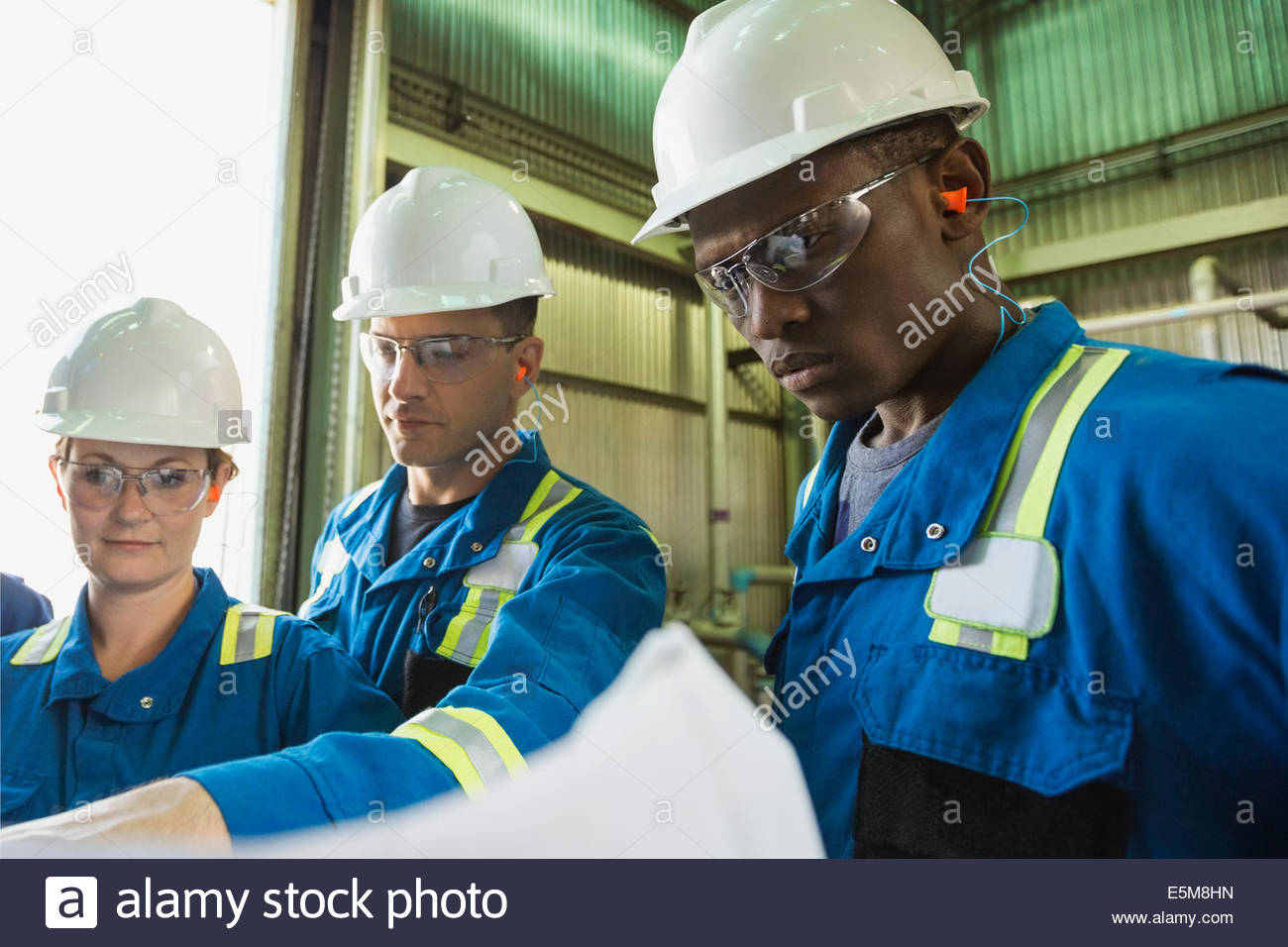 Workers reviewing blueprint in gas plant - Stock Image