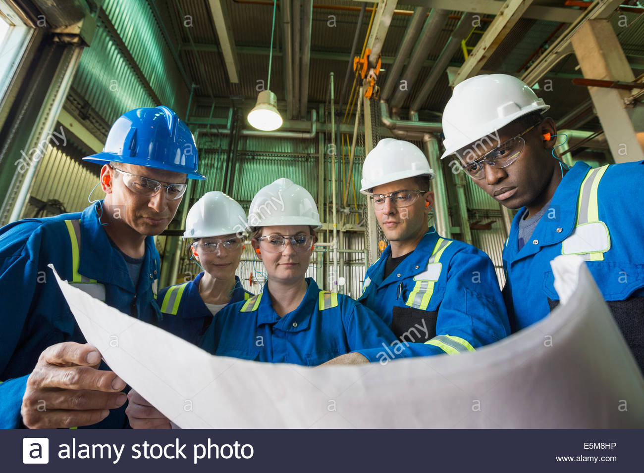 Workers reviewing blueprint in gas plant Stock Photo