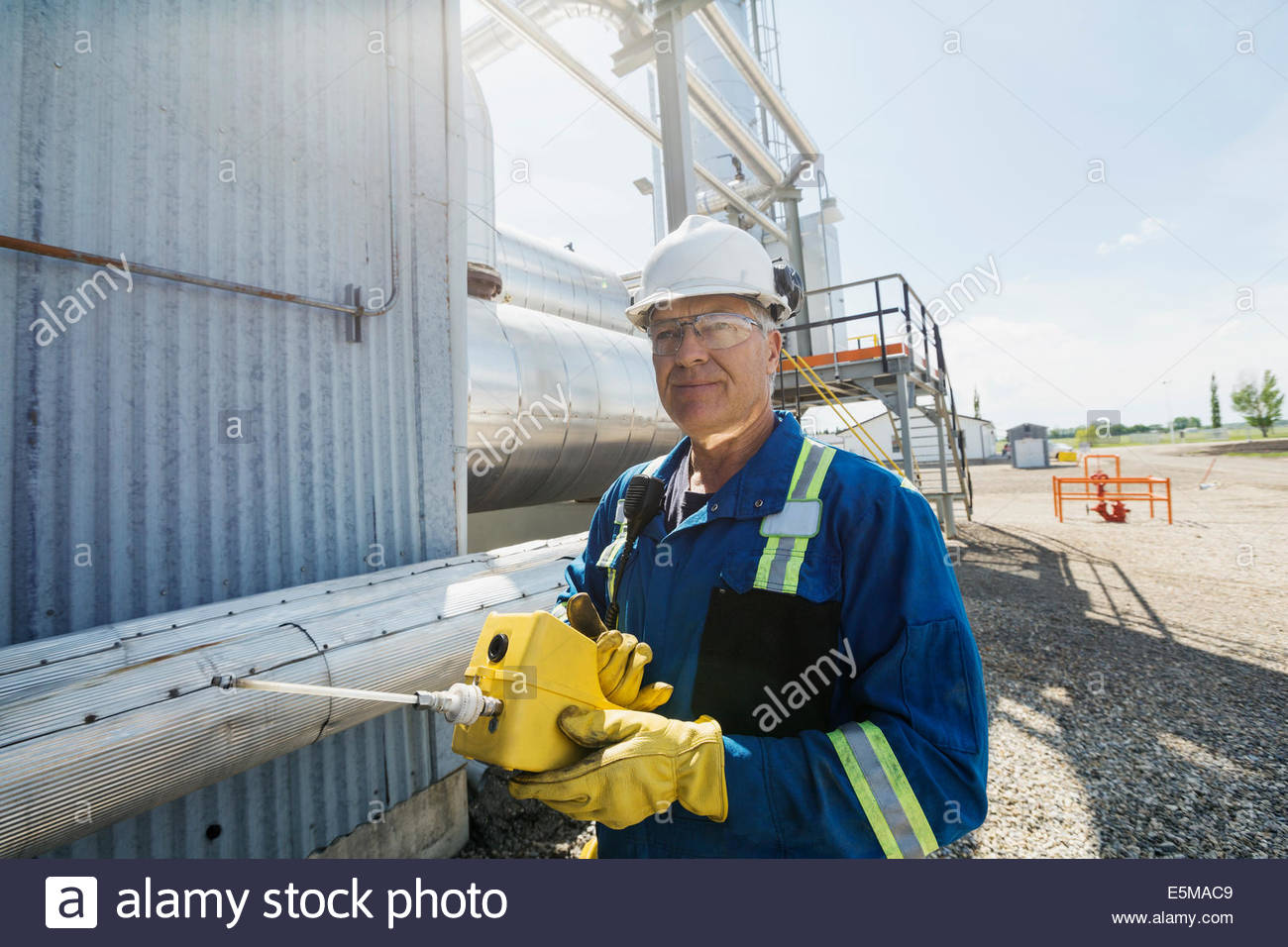 Male worker using monitor at gas plant - Stock Image