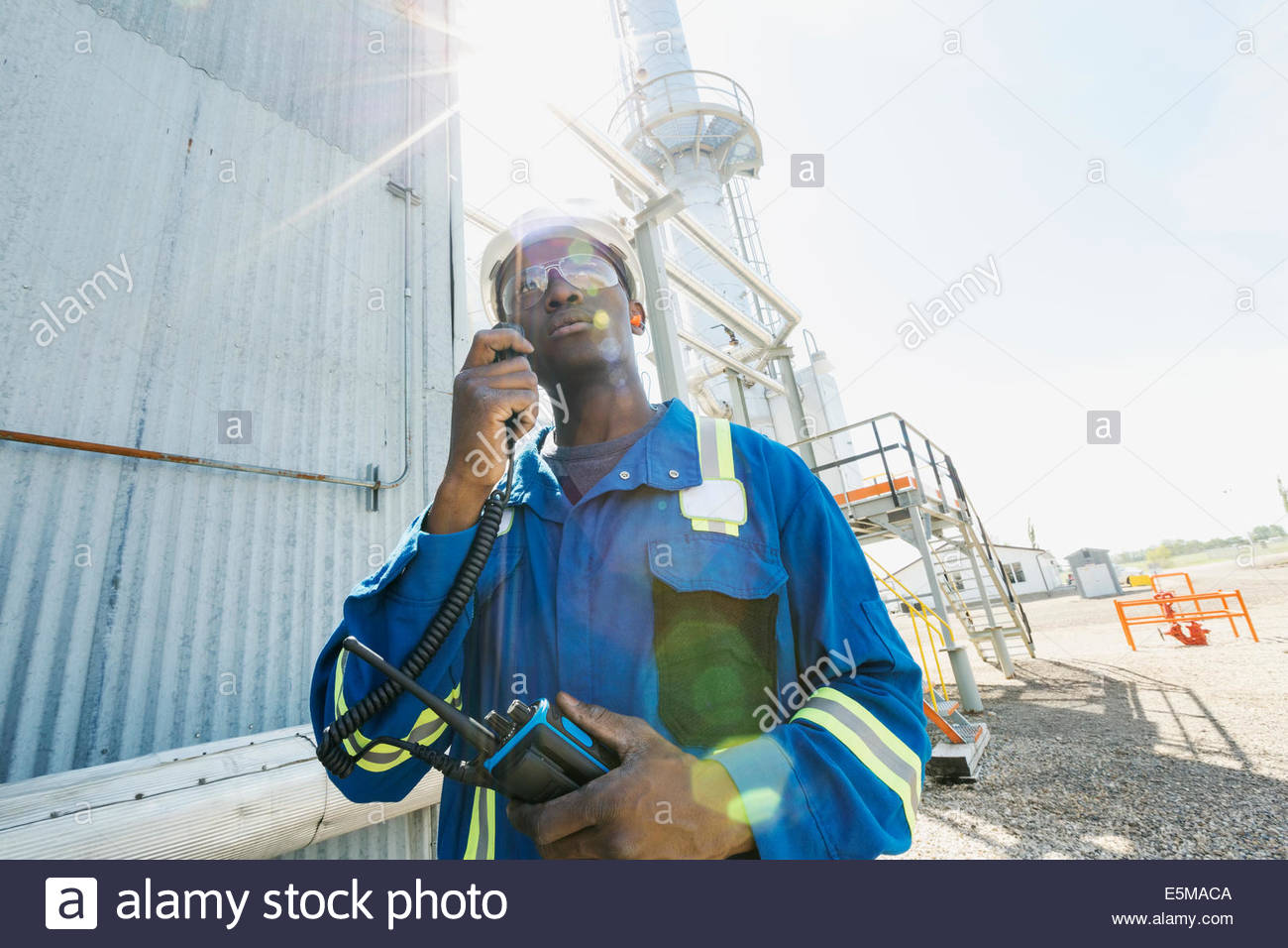 Male worker using walkie-talkie at gas plant - Stock Image