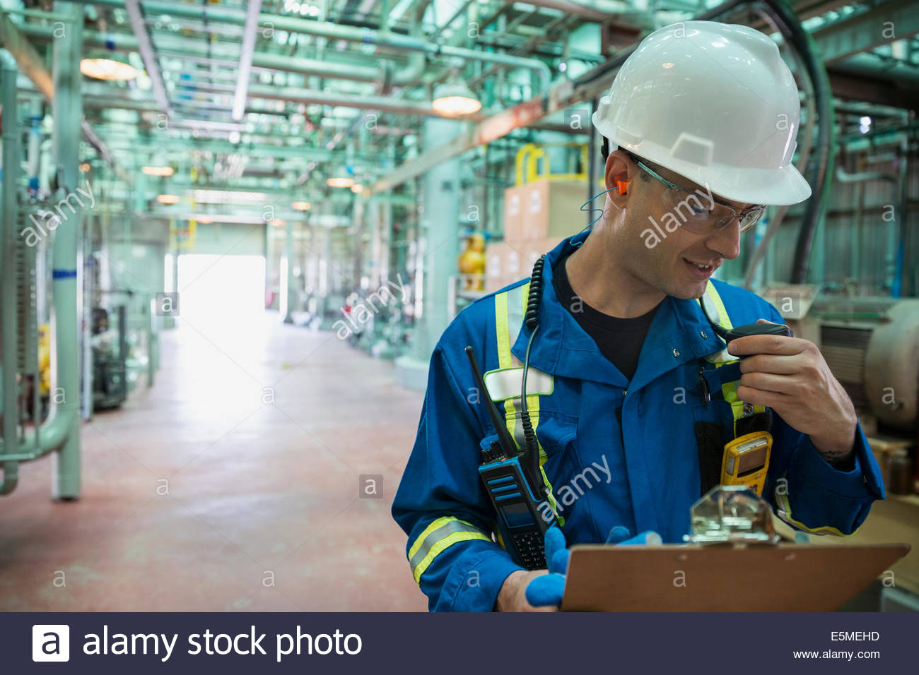 Male worker using walkie-talkie in gas plant - Stock Image