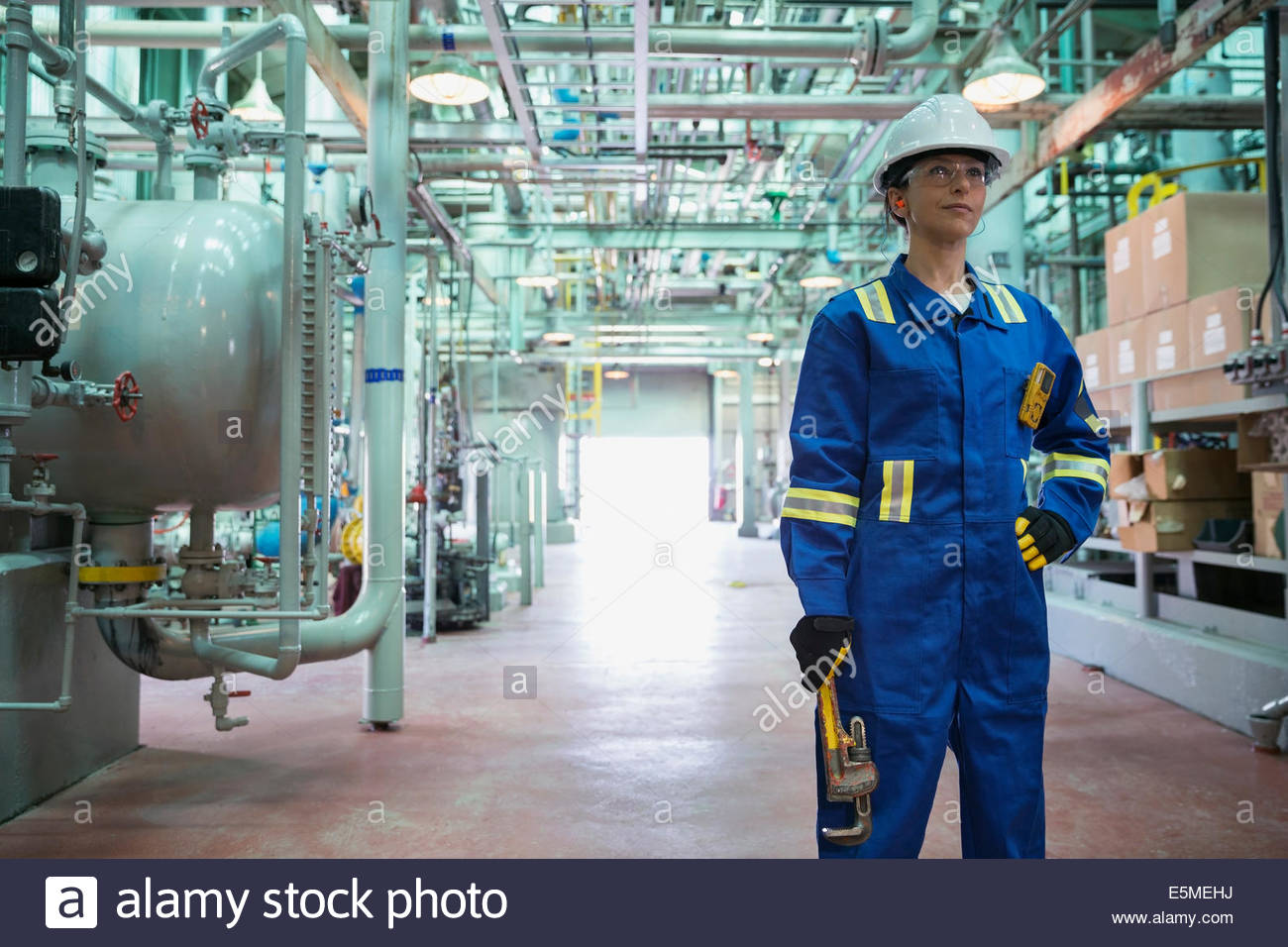 Portrait of confident female worker in gas plant - Stock Image
