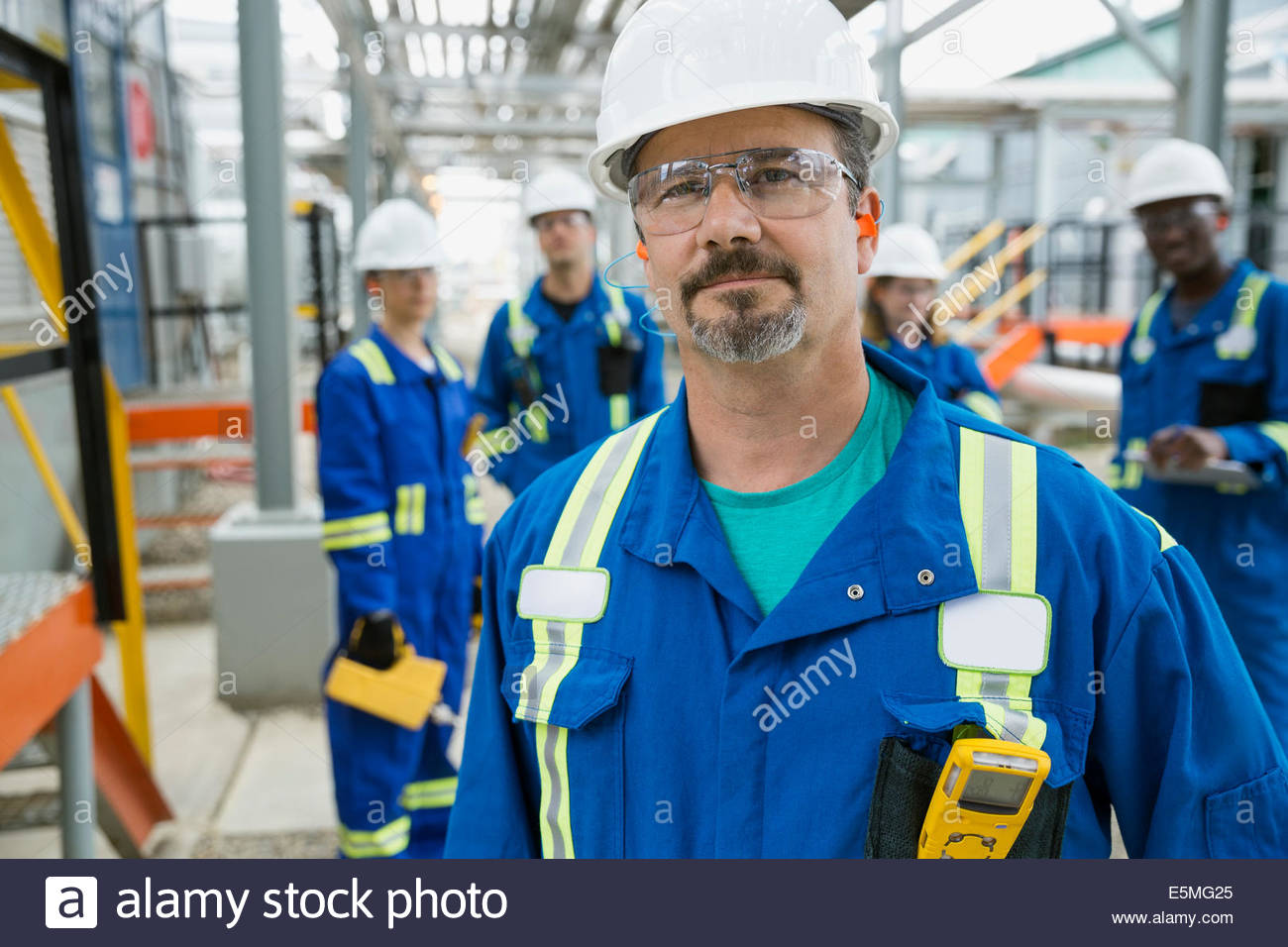 Portrait of confident workers at gas plant - Stock Image