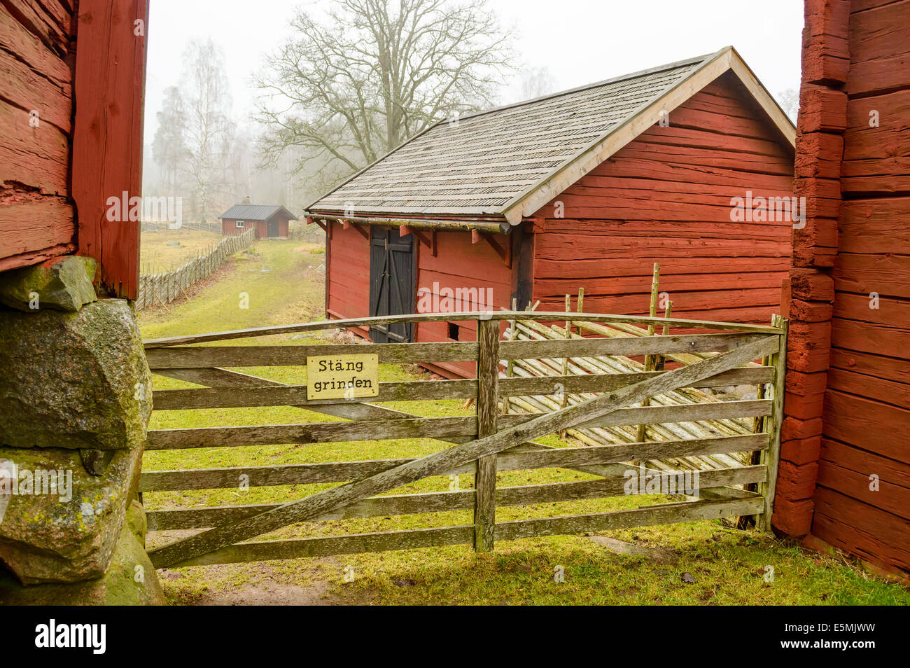 Farm environment in Sweden from around the years 1700 to 1800. Barn and tool house and a closed gate. - Stock Image