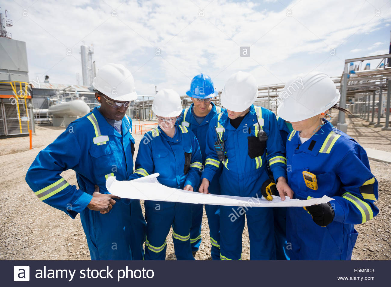 Workers reviewing blueprint outside gas plant - Stock Image