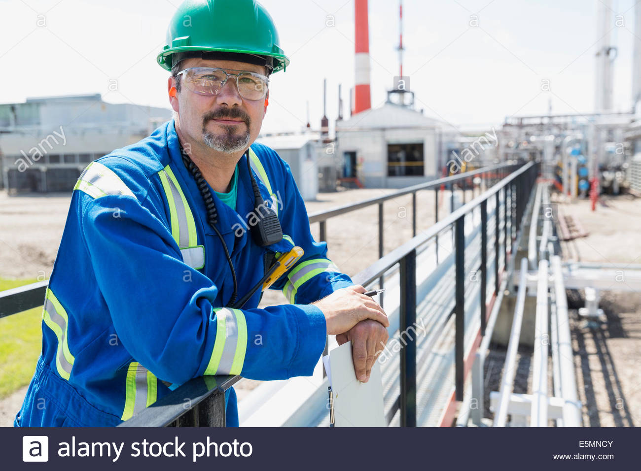 Portrait of worker on platform outside gas plant - Stock Image