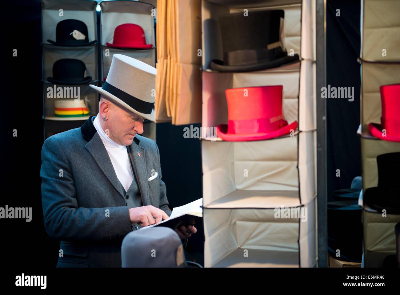 Smart stall holder selling Top Hats, Spitalfields market. East London, UK 2014 - Stock Image