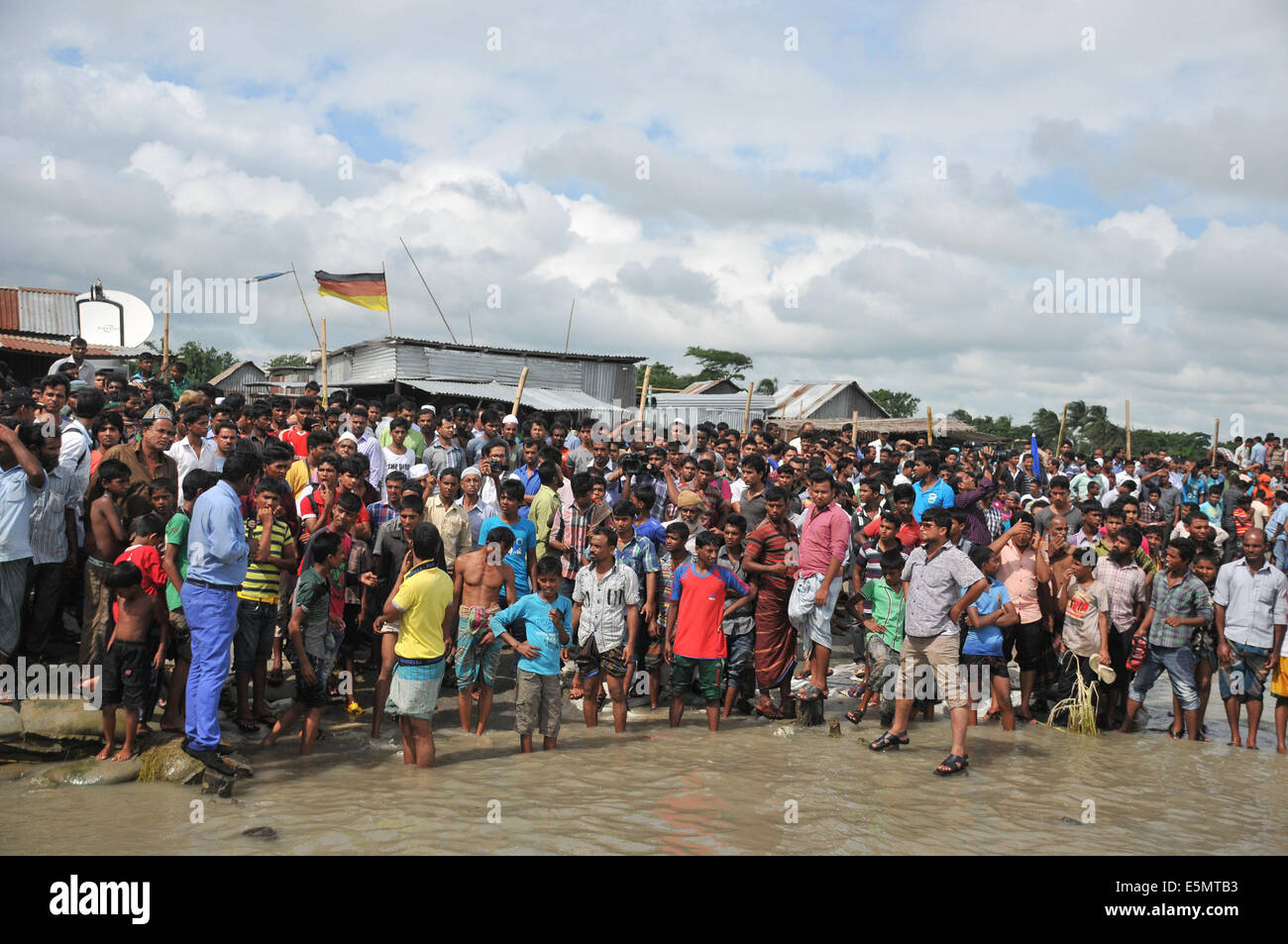 Mawa. 4th Aug, 2014. Local people gather near the site of a ferry accident in Munshiganj district, some 37 km from - Stock Image