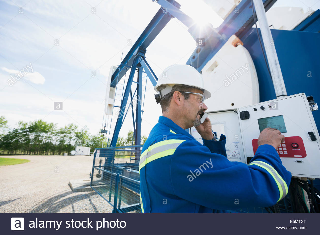Male worker checking oil well equipment - Stock Image