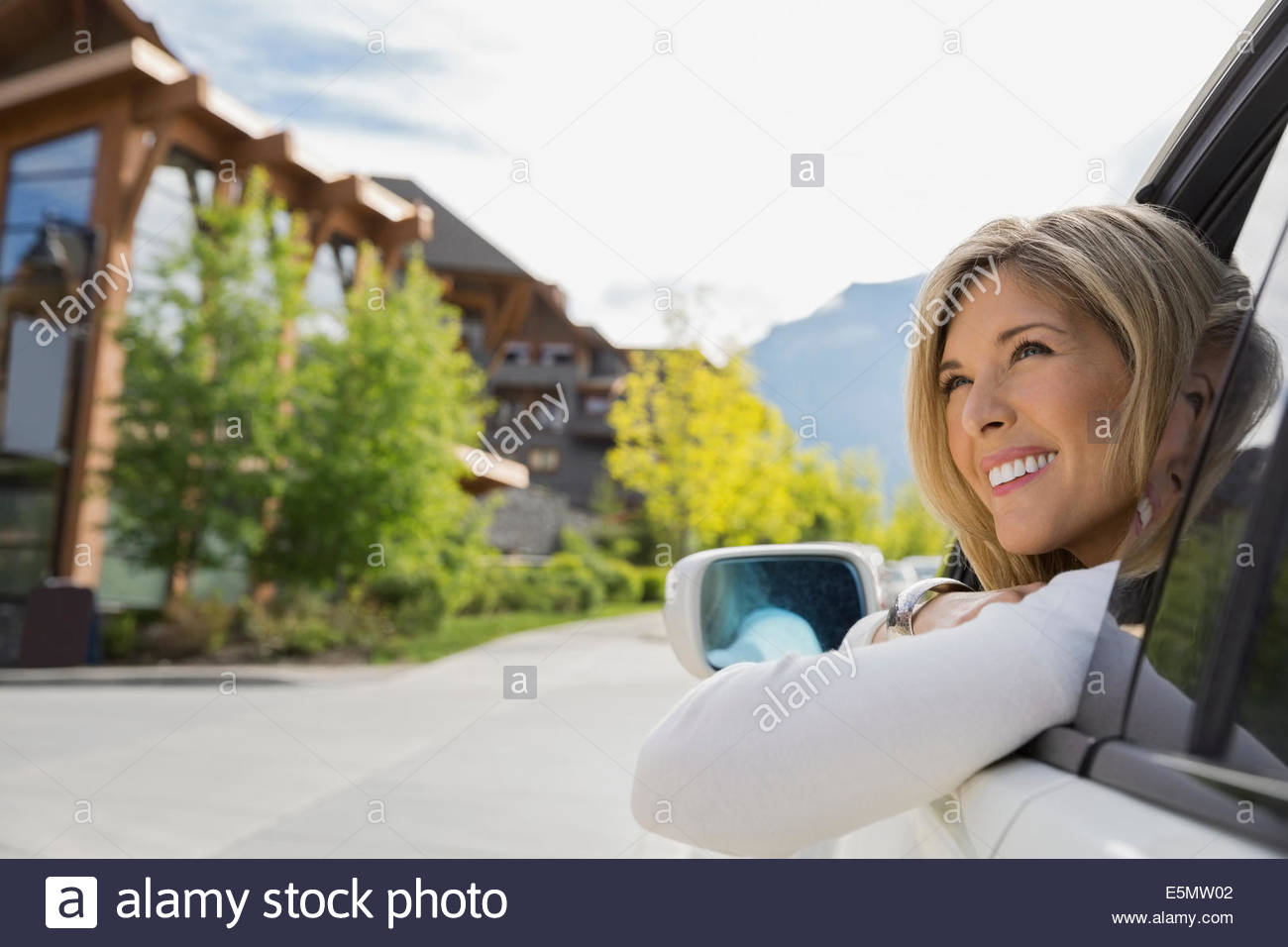 Smiling woman in car arriving at hotel - Stock Image
