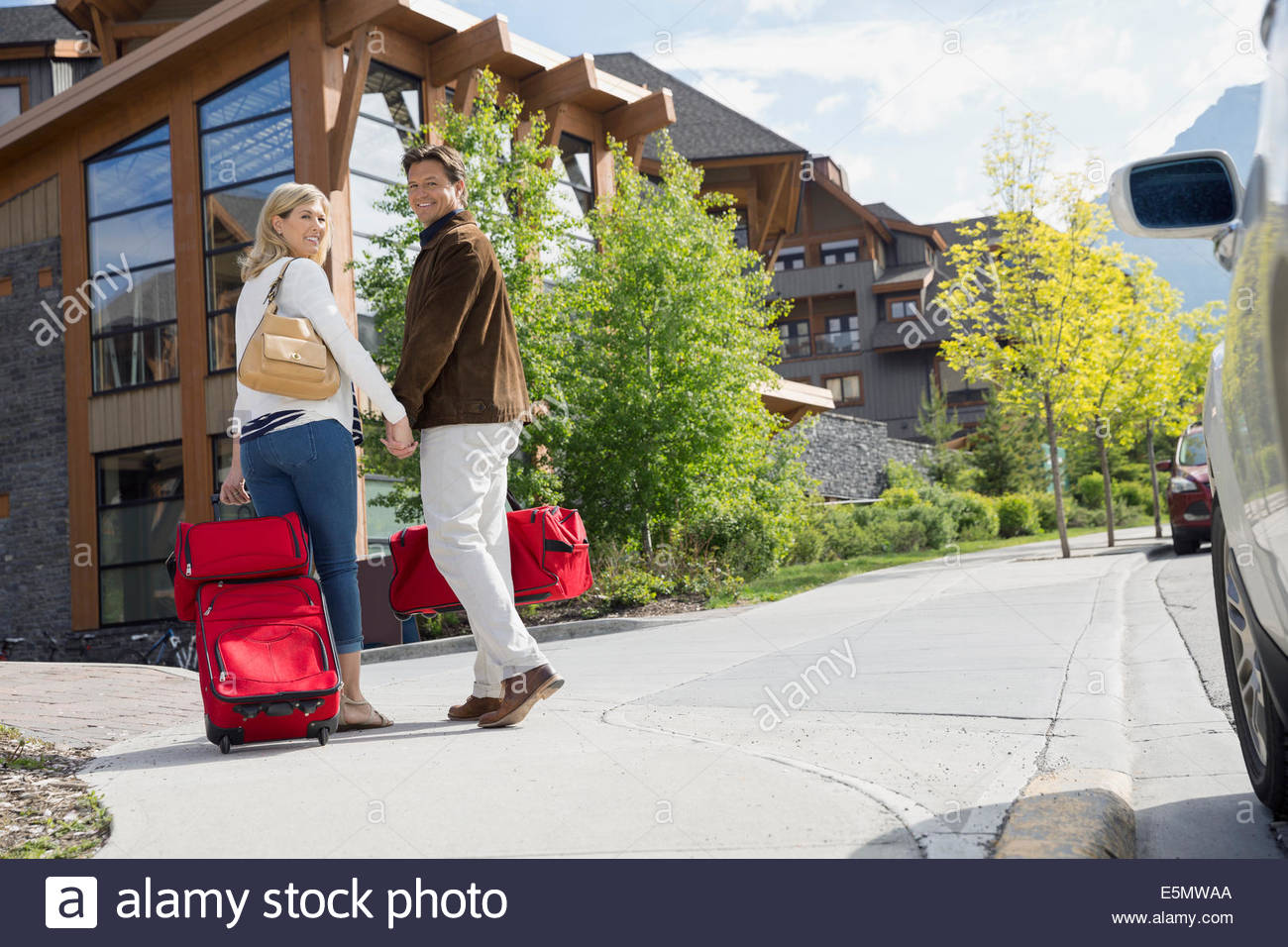 Couple with luggage arriving at hotel - Stock Image