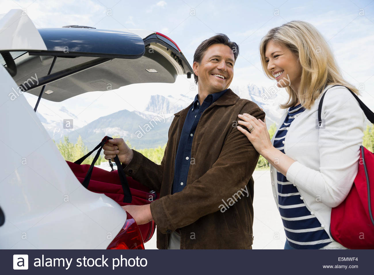 Couple loading luggage in hatchback of car - Stock Image